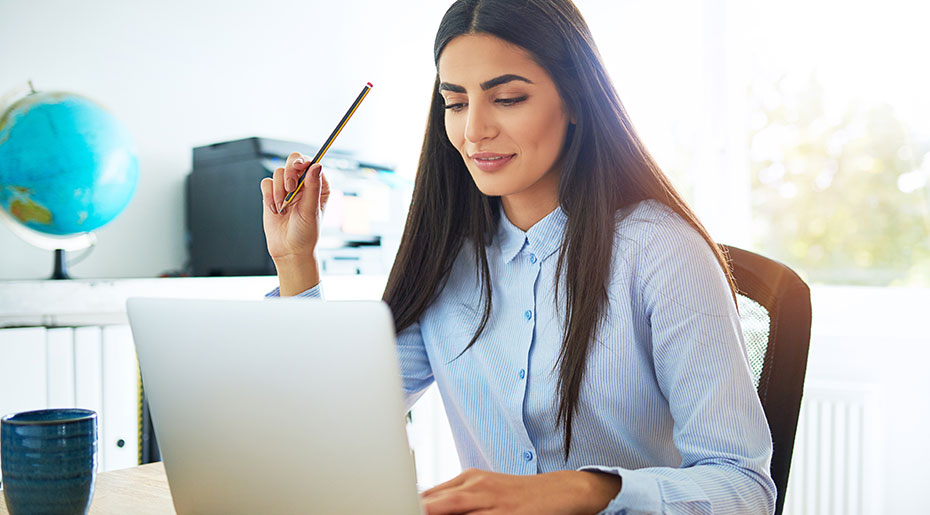 Image of woman on laptop, holding a pencil