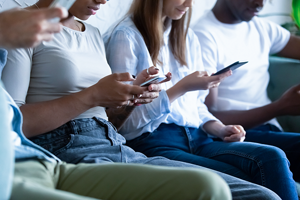 Group image of four individuals sitting down, looking at their mobile phones