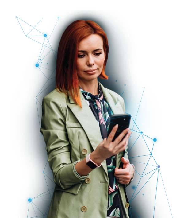 Woman in a green jacket with red hair looking at her cell phone in her right hand.