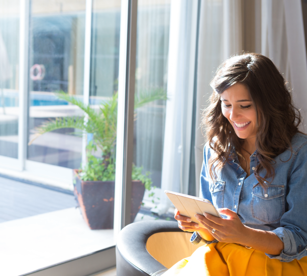 Woman wearing a blue shirt and yellow skirt sitting next to a window, looking down and smiling at a tablet computer she is holding.