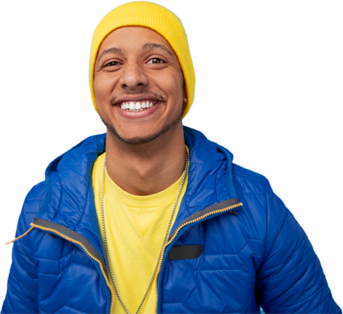 Man in a yellow hat, yellow shirt and blue ski coat looking forward and smiling.