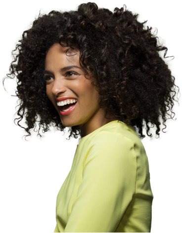 Woman with curly black hair looking to the left and smiling. She is wearing a long sleeved light green shirt.