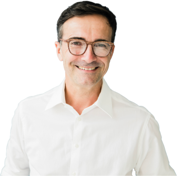 Man with short brown hair wearing glasses and a white button down shirt. He is looking at the camera and smiling.