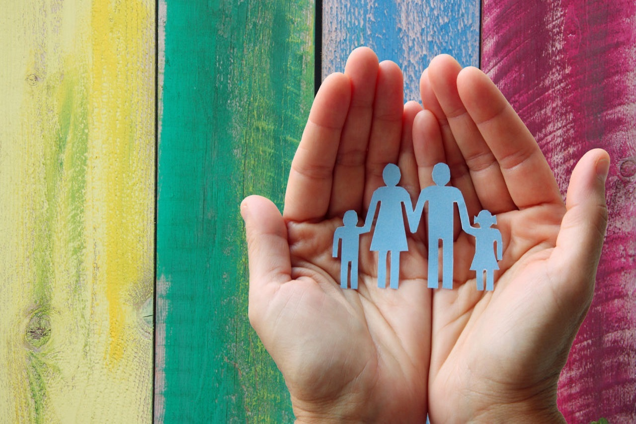 Close-up of hands n front of multicolored wood panels, holding blue cutout of a four person family all holding hands