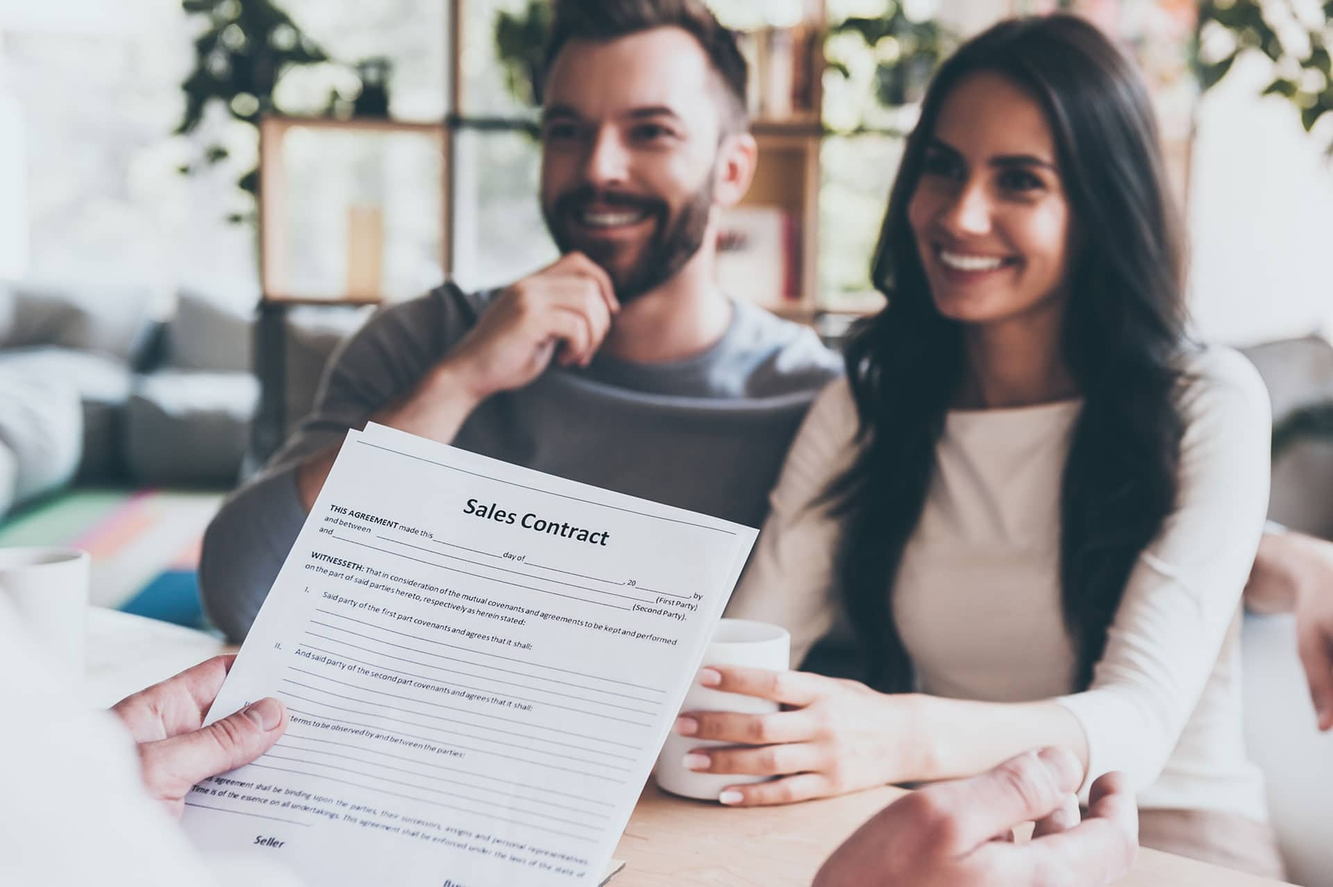 Man with brown hair and a beard and woman with long brown hair are smiling as a hand holds a sales contract in front of them