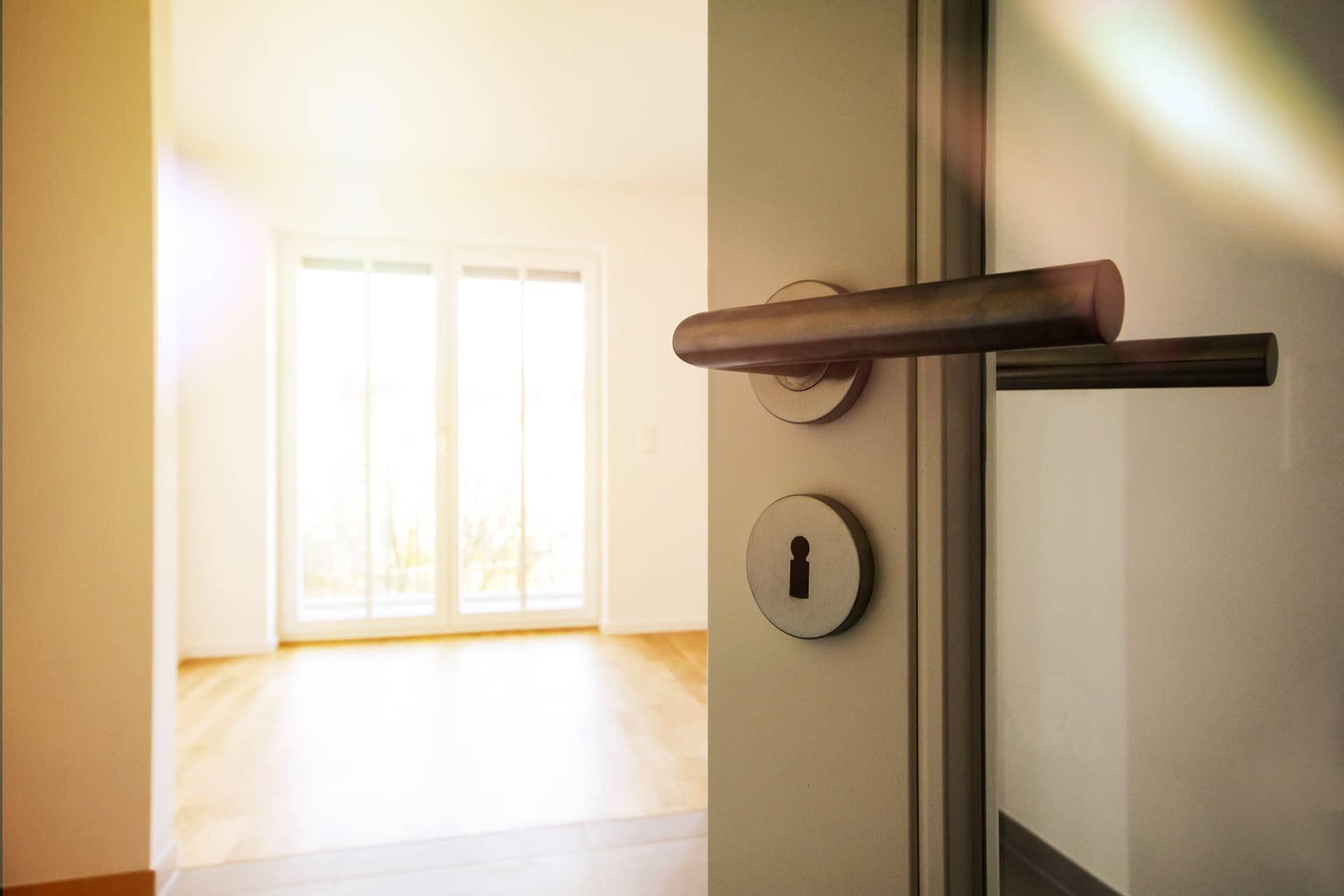 View of empty apartment from open doorframe of glass door. Hardwood floors, sliding glass door in background