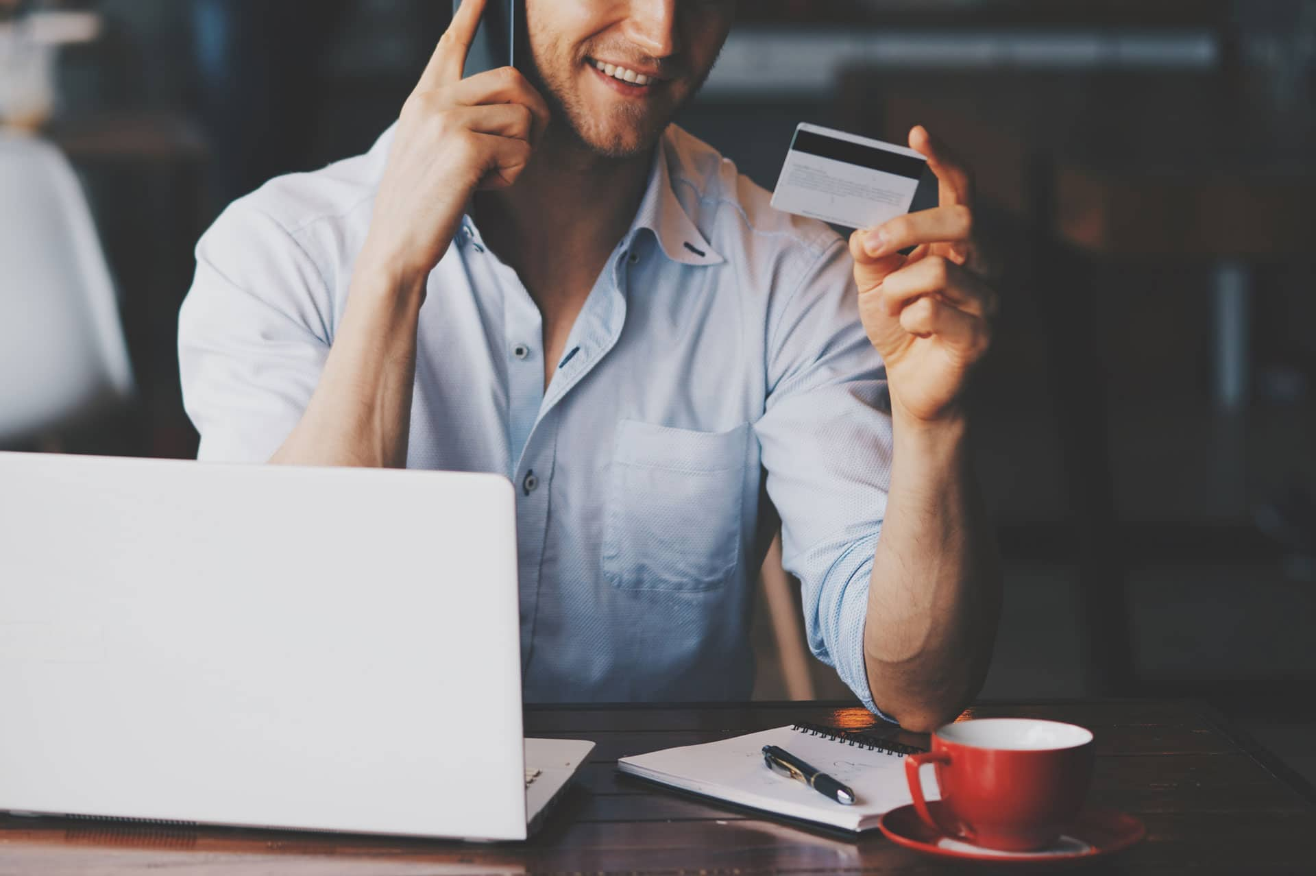 Man sitting at desk with laptop, notebook, pen, red coffee cup in front. He is on phone and holding credit card, smiling