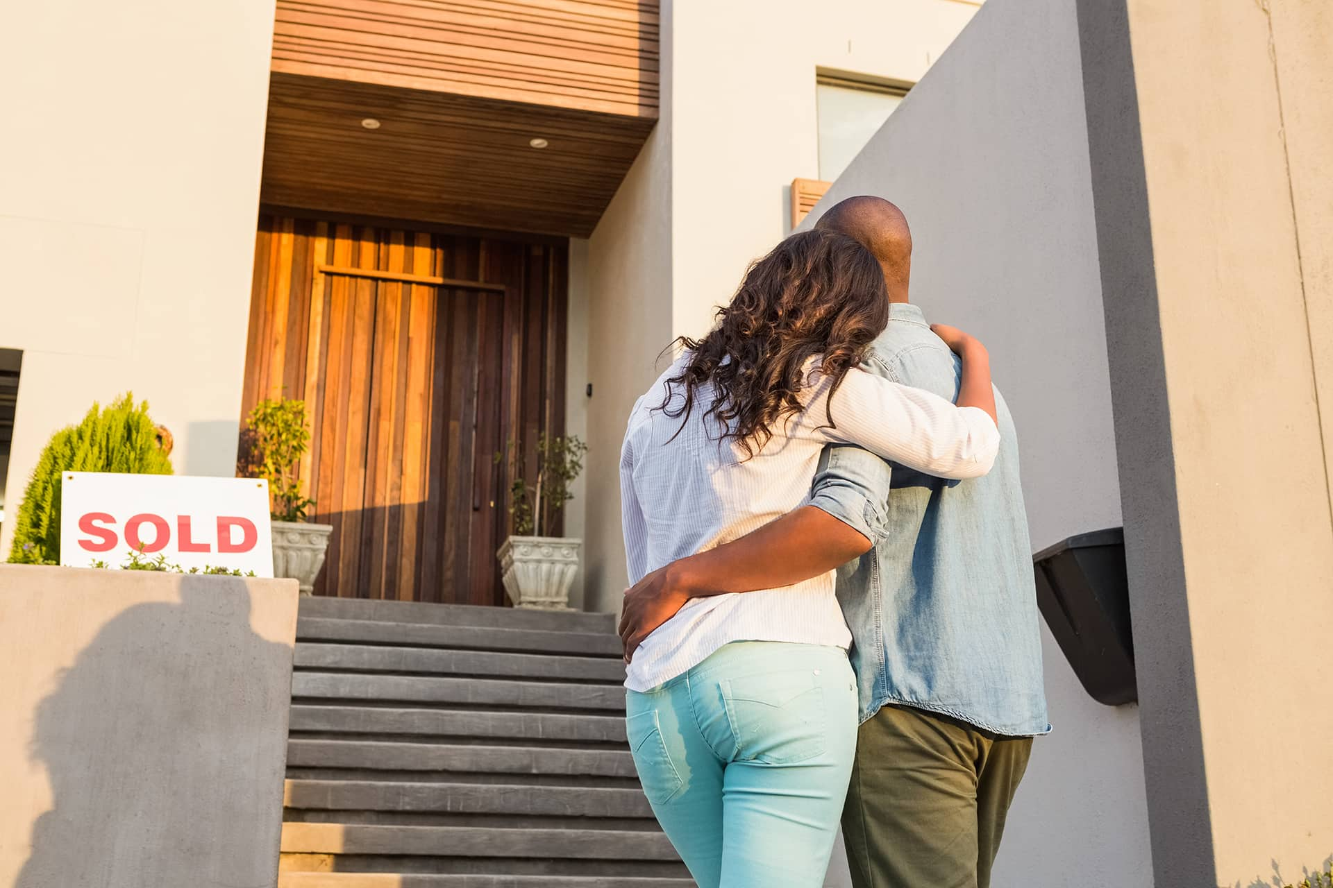 Behind view of young couple with arms around one another, standing at bottom of stairs, looking at front door. SOLD sign