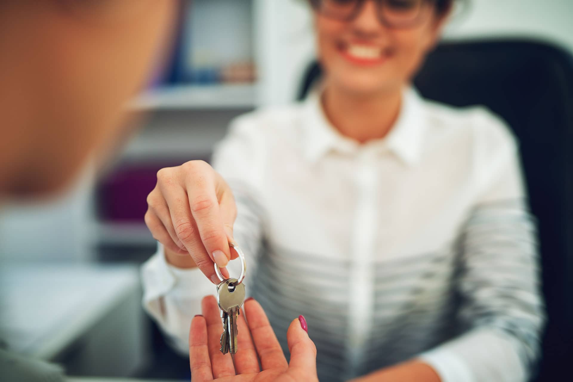 Close up of a young woman in a white shirt and glasses handing keys to an outstretched hand
