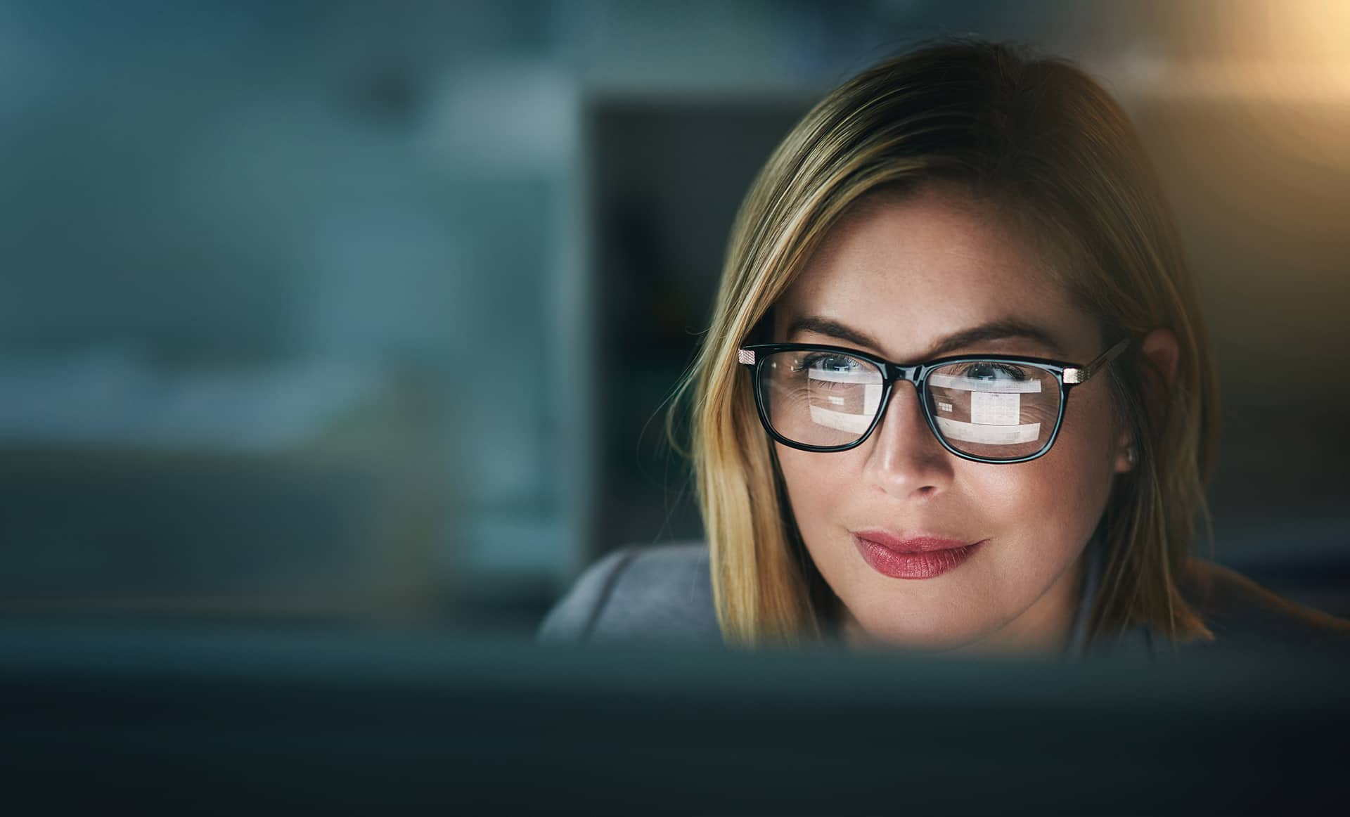 Female case worker with glasses working and looking at laptop.