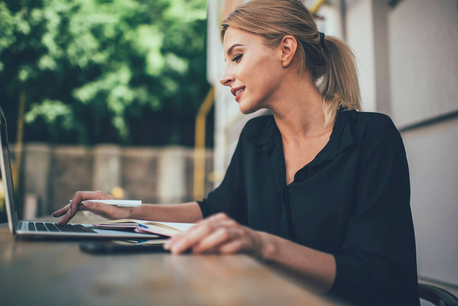Young woman with blond hair in ponytail and black blouse sitting outside looking at laptop on table, pen in hand