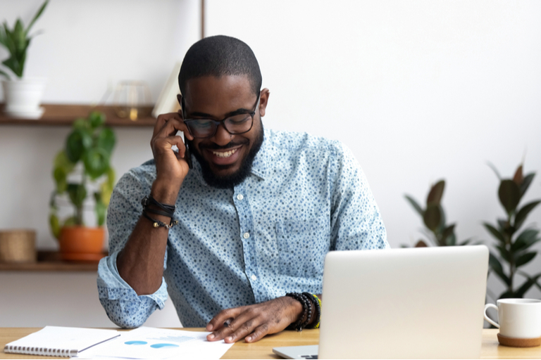 Young Black man in glasses talking on cellphone, smiling at papers on table in front of him. Laptop, coffee mug to the side