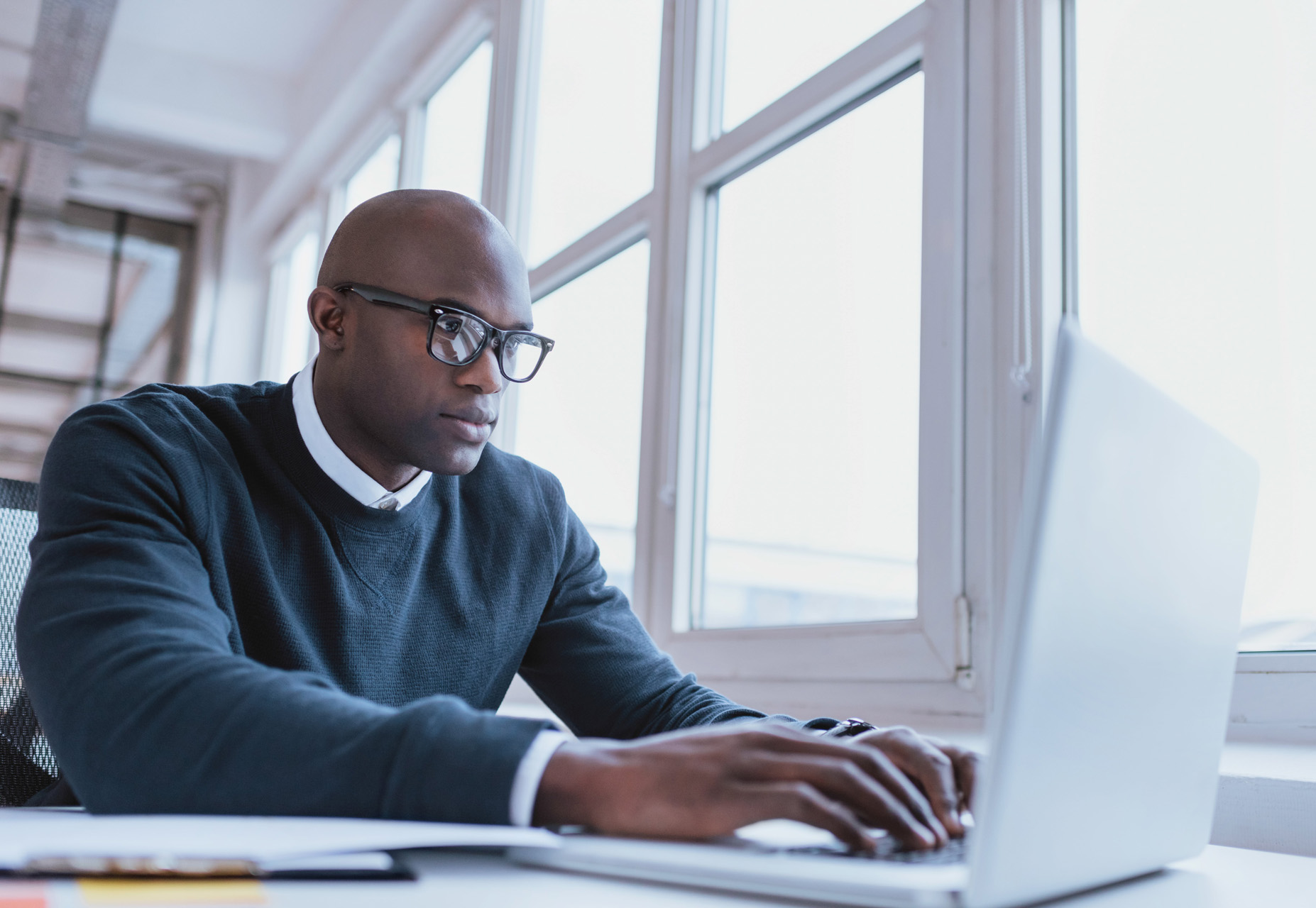 An African-American man in a blue sweater and black glasses is using electronic i9 management software on a laptop next to tall windows.