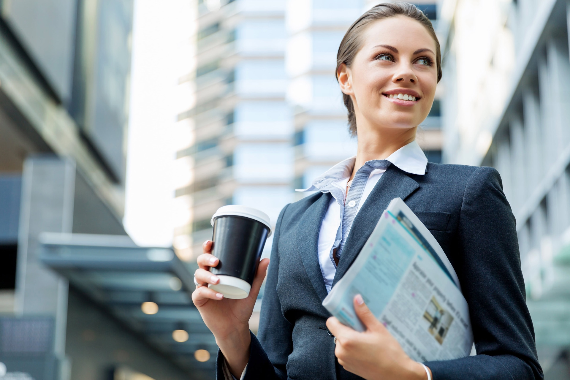 woman wearing a suit, smiling as she carries a coffee cup and a newspaper