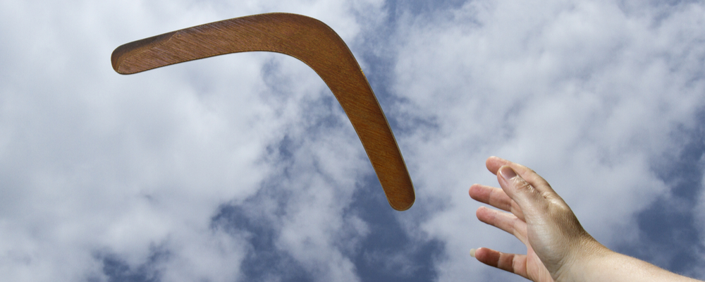 Hand catching boommerang in sky
